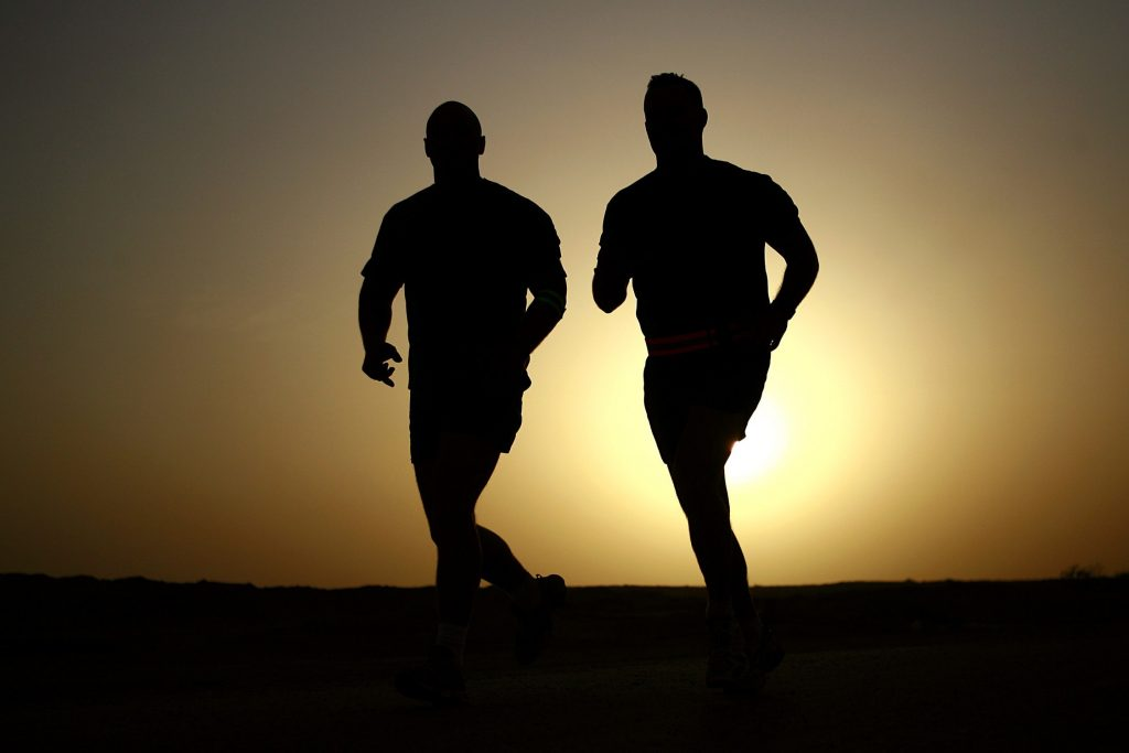 Zwei Männer die joggen im Sonnenuntergang